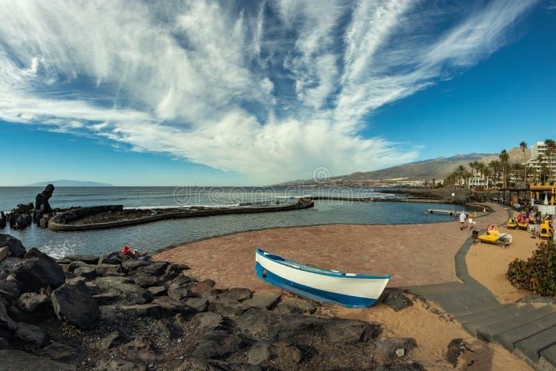 在美洲日报,特内里费岛,西班牙的海岸线 与美丽的云彩的明亮的lue天空 在前景的渔船 拉戈梅拉海岛 库存图片