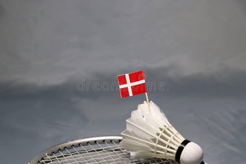 在羽毛球拍上网把放的shuttlecock的微型丹麦旗子棍子在灰色地板上的 库存图片
