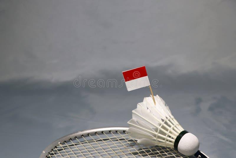 在羽毛球拍上网把放的shuttlecock的微型印度尼西亚旗子棍子在灰色地板上的 免版税图库摄影