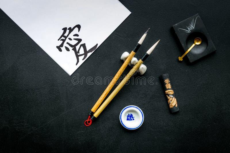 在翻译的中国或日本象形文字在英国手段爱 书法概念 黑背景顶视图 免版税图库摄影