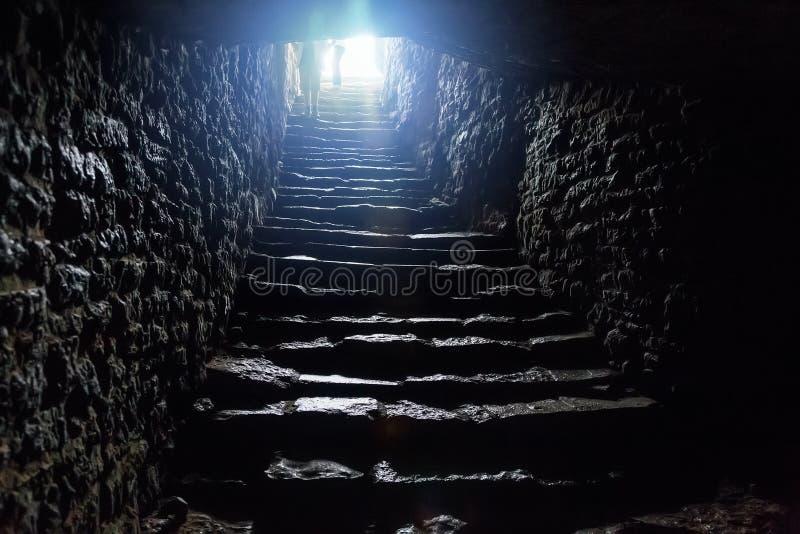在老中世纪堡垒下的地下段落 退出的老石台阶隧道 库存照片