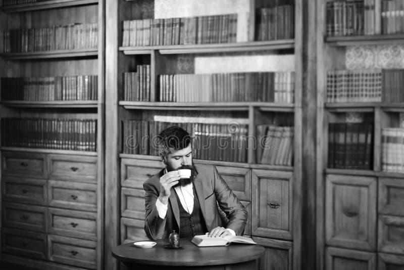 在老书橱附近的成熟人 教育,工作,休闲,咖啡休息,经典样式概念 免版税库存图片