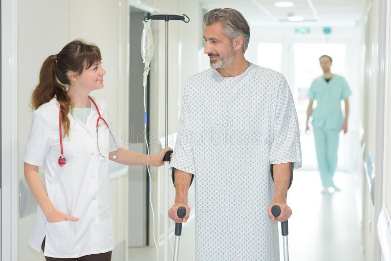 在老人院护理有拐杖的帮助的人 免版税库存照片