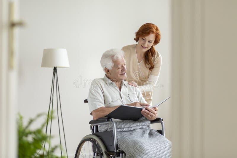 在老人院护理照顾一个轮椅的一个人 免版税库存图片