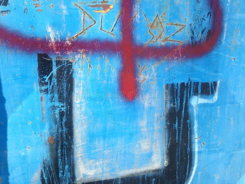 在老公共汽车棚子的红色街道画绘了蓝色 库存照片