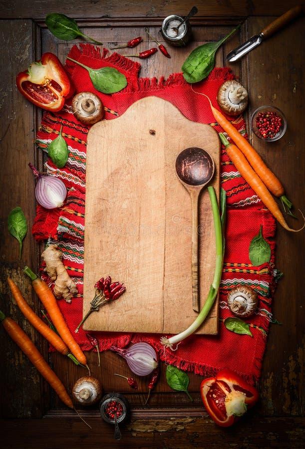 在老切板附近的新鲜的有机菜有在土气餐巾的木匙子和木背景的 顶视图,框架 库存照片