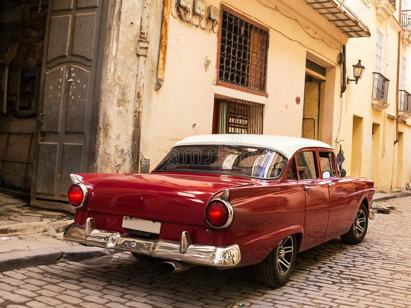 在老哈瓦那古巴路的后面红色老和古典汽车  图库摄影