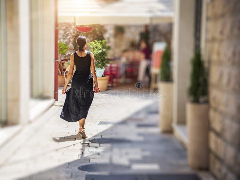 在老城市的街道上的年轻女人一件礼服的在一好日子 库存图片