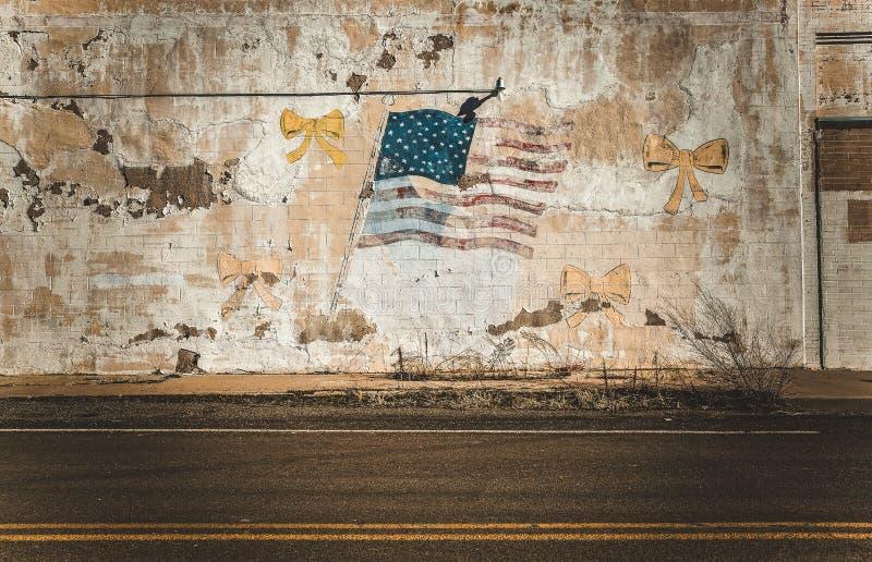 在老墙壁上的美国国旗在被放弃的空的镇 库存照片
