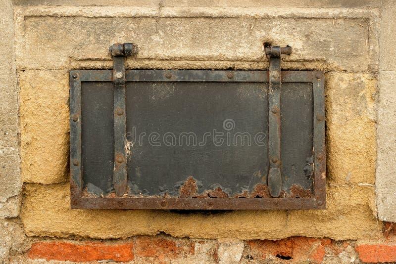 在老墙壁上的老小生锈的膳食舱口盖盖子 库存照片