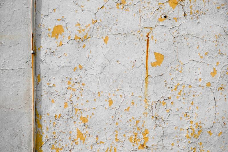 在老墙壁上的黄色导线有削皮膏药的 库存照片
