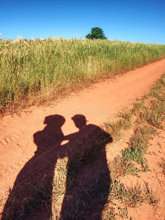 在老多灰尘的路的人阴影有铁红色土壤的 ?? 免版税库存照片