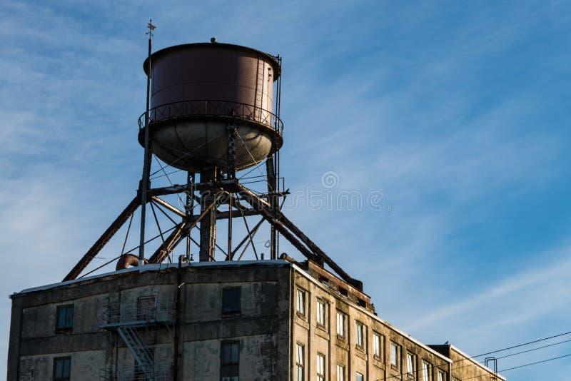 在老大厦屋顶的水塔  免版税库存照片