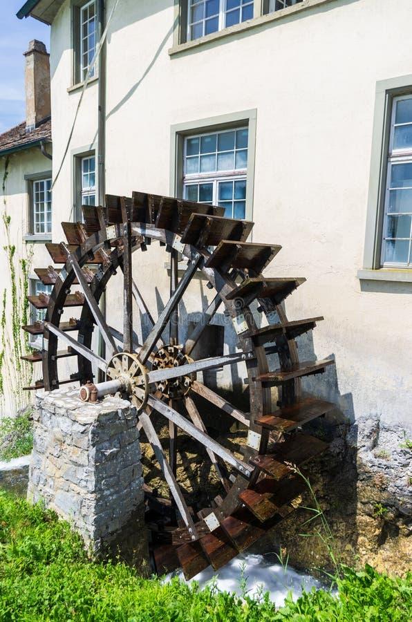在老大厦旁边的老水车轮子在沙夫豪森瑞士好日子 免版税图库摄影