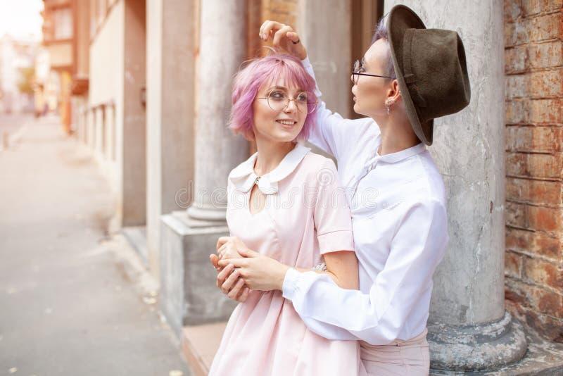 在老大厦附近的两个拥抱的女孩在城市 免版税库存照片