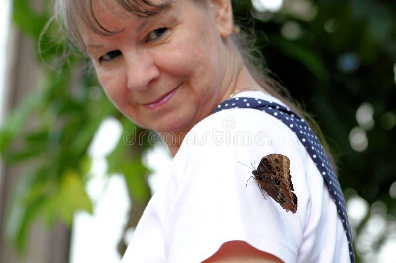 在老妇人胳膊的蓝色Morpho蝴蝶 免版税库存照片