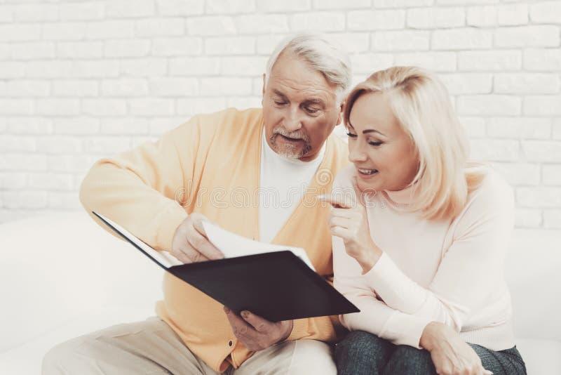 在老妇人附近的老人有在文件夹的文件的 免版税库存图片