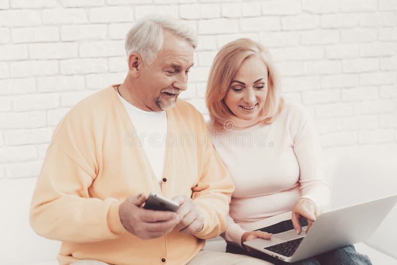 在老妇人附近的老人有智能手机和膝上型计算机的 库存图片