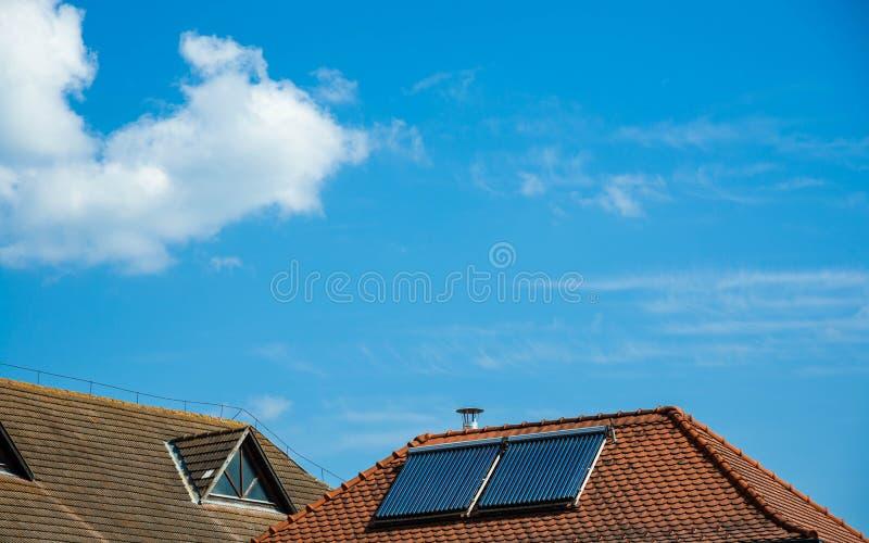 在老屋顶,与白色云彩的蓝天的太阳水加热器 免版税库存照片