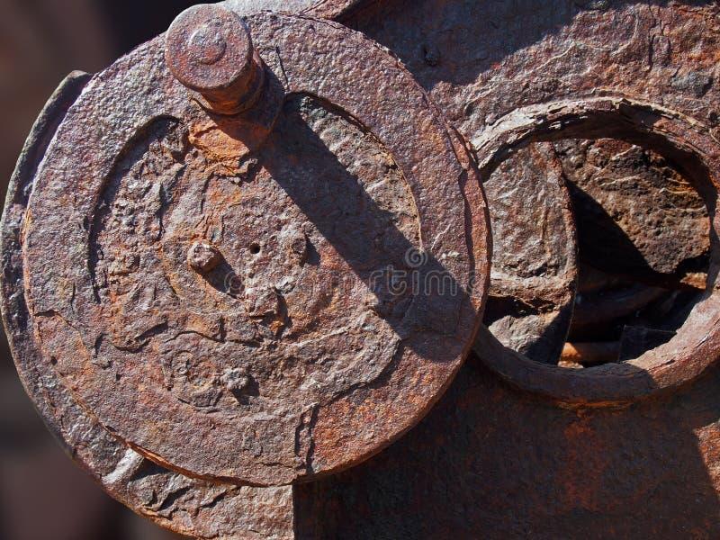 在老工业机械的棕色铁锈盖的被腐蚀的铁轮子 免版税库存图片
