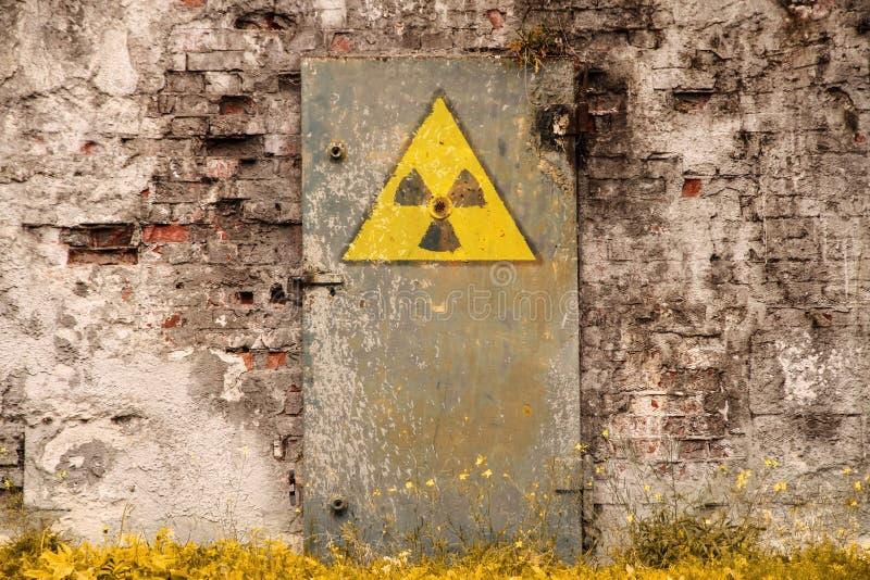 在老巨型的生锈的铁门绘的放射性致电离辐射危险标志 免版税库存照片