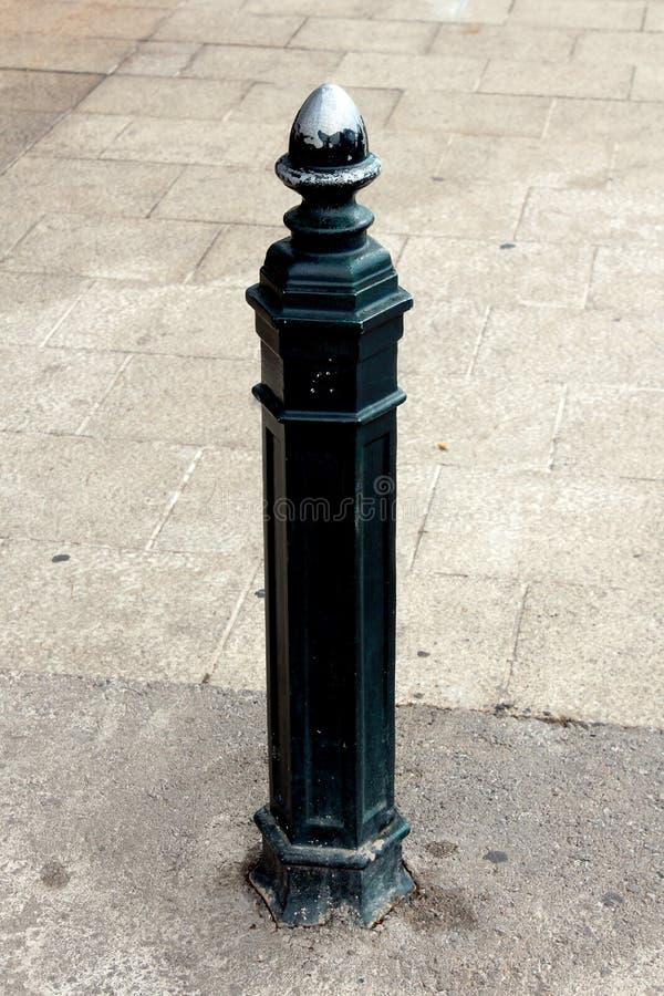 在老巴洛克式的样式的锻铁杆与破裂和被洗涤的油漆用于作为篱芭一部分防止未批准的停车处 库存图片
