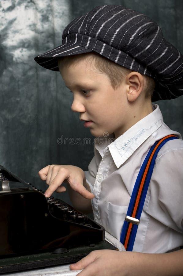 在老打字机的男孩文字 免版税图库摄影