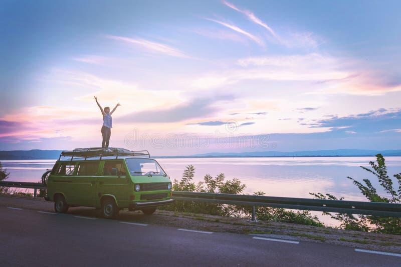 在老朋友经典露营者货车屋顶的年轻美女身分有惊人地五颜六色的日落天空的,ha海停放的 库存图片