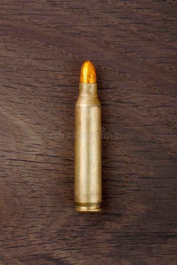 在老木书桌上的老步枪子弹 库存照片