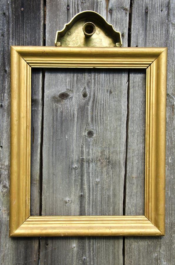 在老木墙壁上的葡萄酒金黄木画框 免版税库存图片