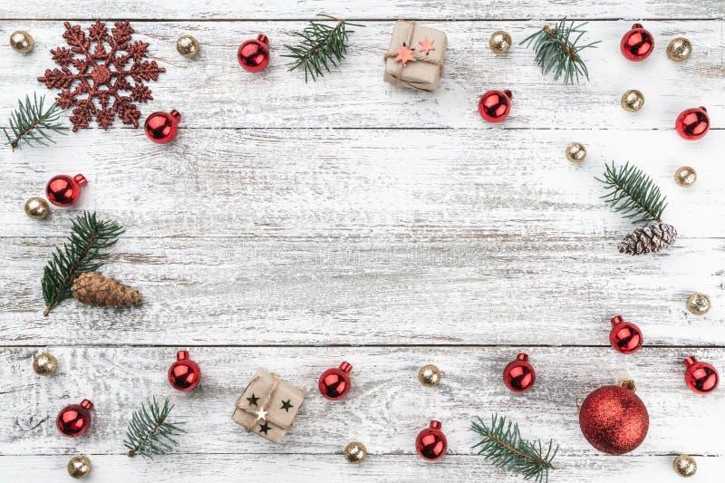 在老木头圣诞节背景的框架  红色和金中看不中用的物品 分支锥体冷杉 Xmas项目 顶视图 免版税图库摄影