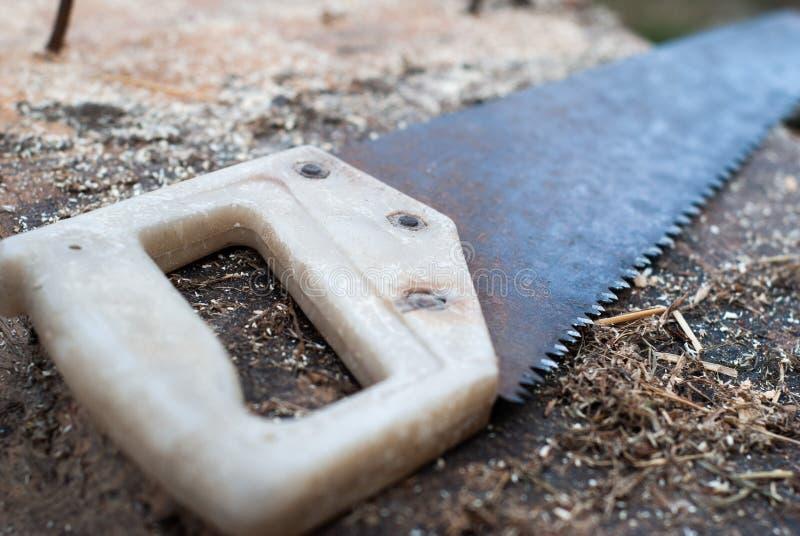 在老木头的老锯,生锈的齿状的锯, 免版税库存照片
