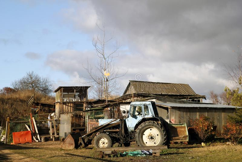 在老木房子附近的老蓝色生锈的拖拉机 库存照片