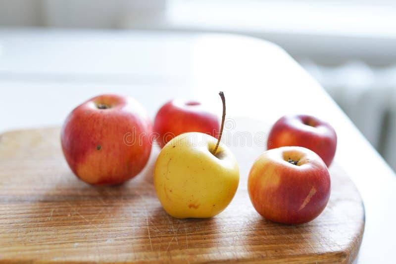 在老木板的红色新鲜的苹果在轻的背景在白色厨房里 健康的食物 库存图片