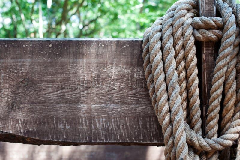 在老木板背景的重绳索在难看的东西样式的 作为背景诱饵概念美元灰色吊异常分支 老美国牛仔,大农场,套索 de的背景 免版税库存照片