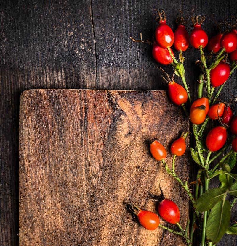 在老木板,顶视图,秋天背景的野玫瑰果 免版税图库摄影