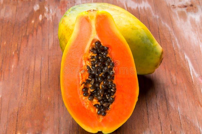 在老木桌上的切的新鲜的番木瓜 免版税库存图片