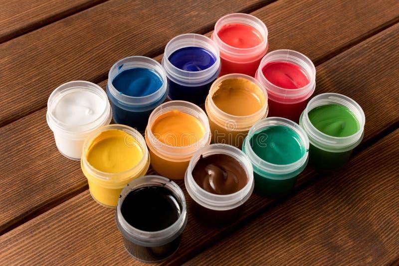 在老木桌上的各种各样的油漆 创造性的概念 图库摄影