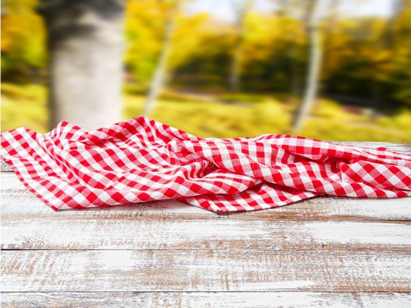 在老木桌上的方格的桌布在被弄脏的公园背景,假日概念 库存图片