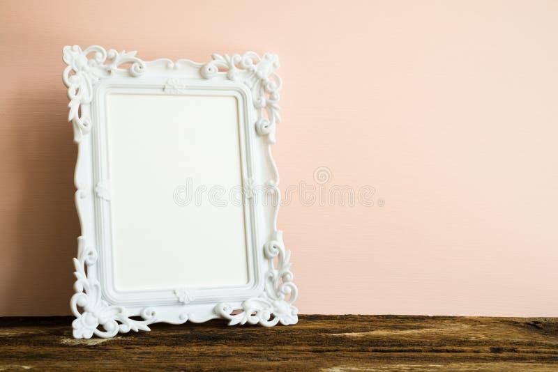 在老木桌上的白色葡萄酒照片框架在桃红色墙壁bac 库存图片