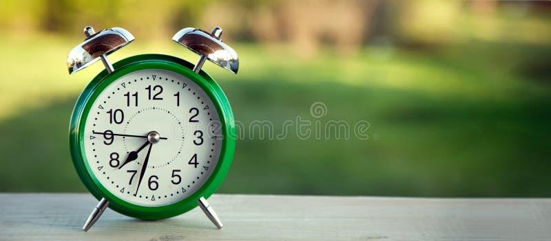 在老木桌上的绿色时钟在晴朗的夏天庭院里 库存图片