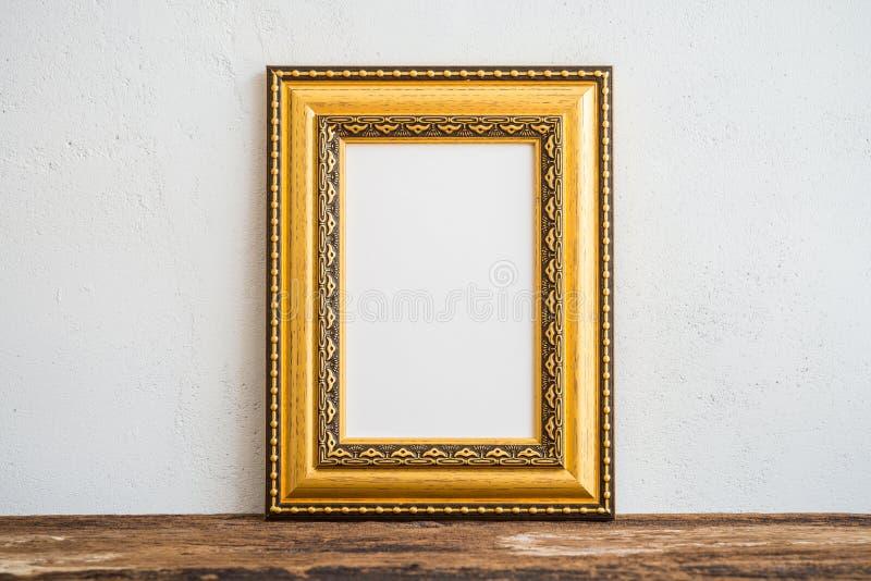在老木桌上的金黄葡萄酒照片框架在白色墙壁b 免版税库存照片