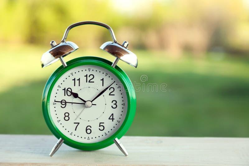 在老木桌上的绿色时钟在晴朗的夏天庭院里 库存照片