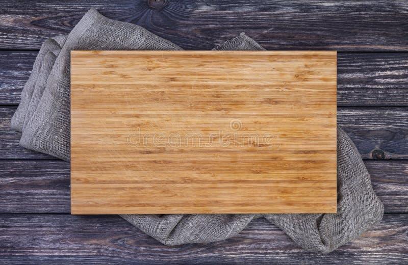 在老木桌,在黑暗的木背景,顶视图的切板的服务盘子 库存照片