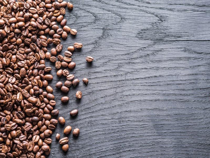 在老木背景的烤咖啡豆 顶视图 库存图片