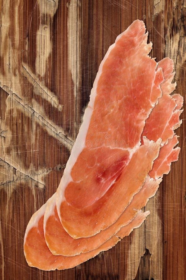 在老木背景的熏火腿切片 免版税库存图片