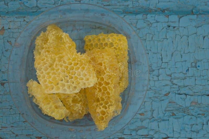 在老木背景的黄色蜂窝塑料盘无危险绘了油漆 库存照片