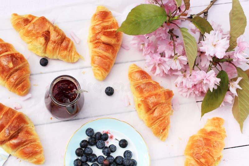 在老木背景,浪漫早餐的新鲜的法国新月形面包在庭院里 免版税库存图片