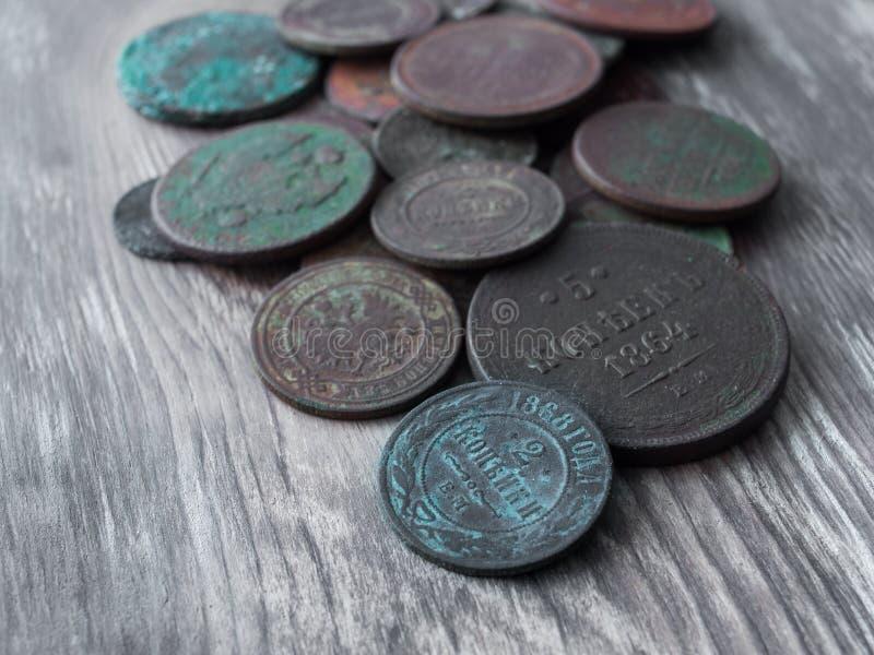 在老木头背景的硬币  免版税库存图片