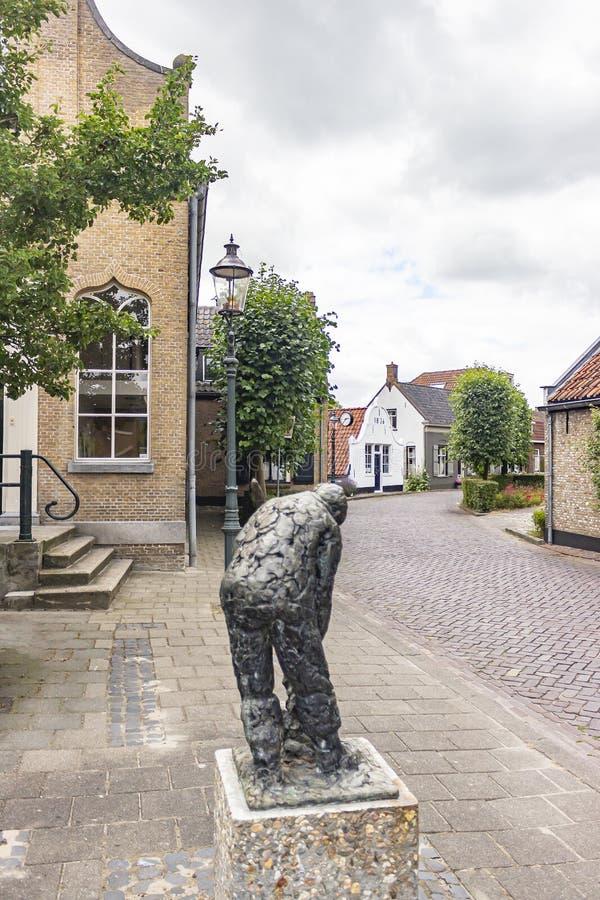 在老村庄前面的一个雕象在Drimmelen,荷兰美丽如画的村庄  图库摄影